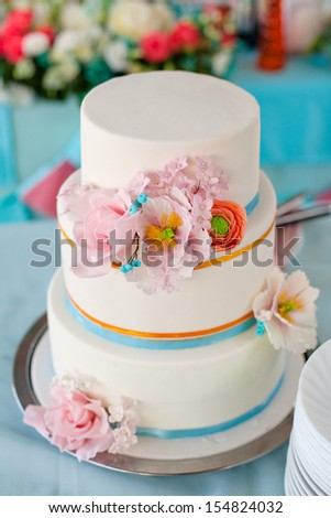 White Wedding Cake with Roses and ribbon - stock photo