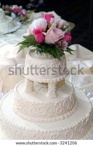 white wedding cake with roses on the top layer