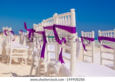 White wedding chairs decorated with purple bows on beach - stock photo