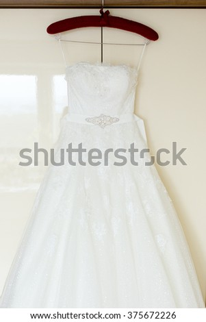 White wedding dress embroidered with beads hanging on wardrobe