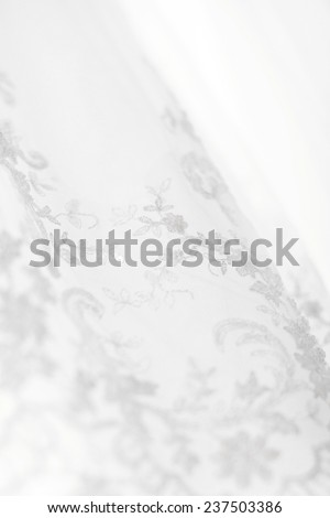 White Wedding dress hanging on a shoulders. Soft light and colours