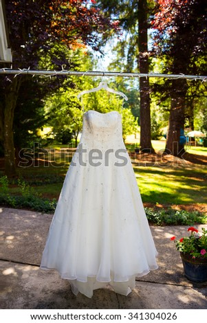 White wedding dress hanging outdoors from some lights.