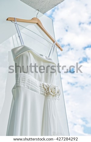 White wedding dress on front of light wall with decorations closeup