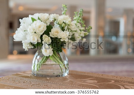 White wedding flower in a clear jar on beautiful table.  - stock photo