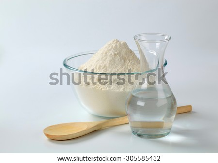 white wheat flour in a glass bowl and a carafe of cold water
