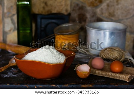 White wheat flour in ceramic ware, broken egg with the yolk, whole eggs and cooking utensils for cooking dough on a background of a stone oven. Rustic style. Side view close-up. Selective focus. - stock photo
