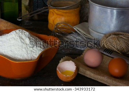 White wheat flour in ceramic ware, broken egg with the yolk, whole eggs and cooking utensils for cooking test. Rustic style. Side view close-up. - stock photo