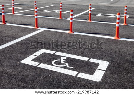 White wheelchair icon on a gray asphalt parking lot - stock photo