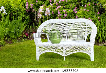 White wicker love seat with watering can in the summer garden. - stock photo