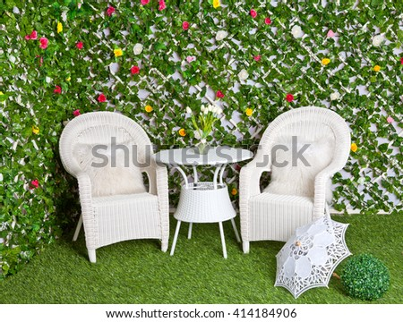White wicker rattan furniture in the blooming garden. Vintage tracery umbrella - stock photo