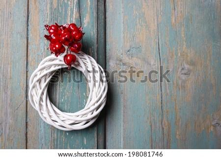 White wicker wreath on wooden door - stock photo