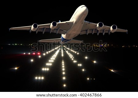 White wide-body passenger aircraft departs from the night airport. Take-off from the highlighted runway. - stock photo
