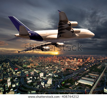 White wide-body passenger plane flying over the city. The sun goes below the horizon, painting the city and the aircraft in fiery sunset colors. - stock photo