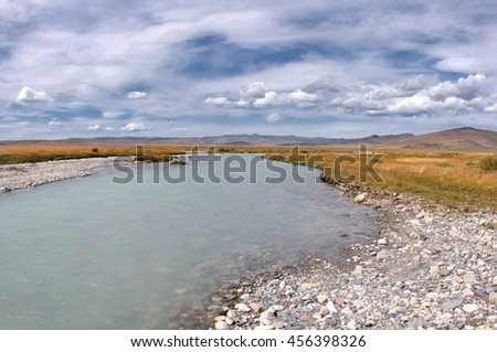 White wide river under white clouds and blue sky, Plateau Ukok, Altai mountains, Siberia, Russia