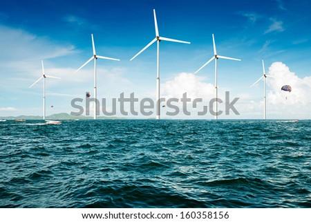 white wind turbine generating electricity on sea - stock photo