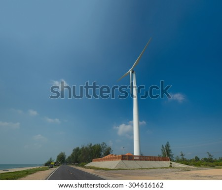 White wind turbine generating electricity on the ocean beach with blue sky - stock photo