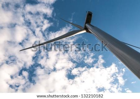White wind turbine on blue sky background - stock photo