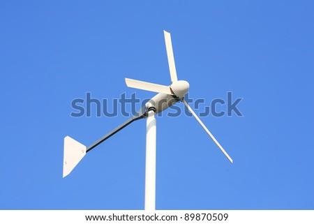 white wind turbine on clear blue sky. - stock photo