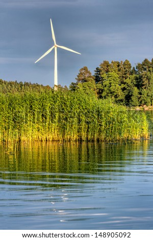 White wind turbine rotating in a sea shore green and blue landscape with evening sunlight and dark clouds - wind energy, sustainability and ecological concept background - stock photo