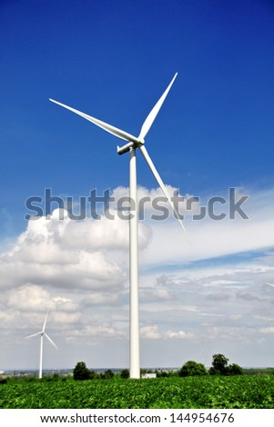 White wind turbines generating electricity and blue sky
