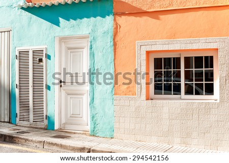 White window and door with stone decoration on vibrant multicolored wall. Canary Islands, Tenerife. Spain. Outdoors image. - stock photo