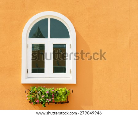 White window and flower hanging with orange wall - stock photo