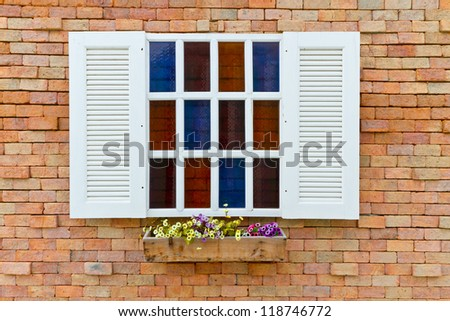 white window with flower on brick wall - stock photo