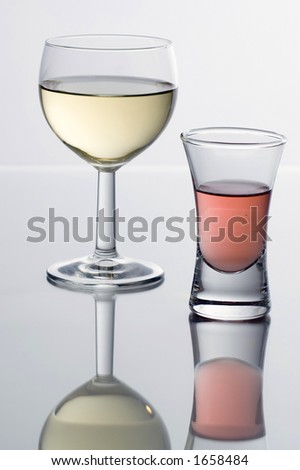 White wine and a vodka schnapps on a glass table