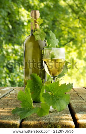 white wine and grapevine leaves in a rural scenery