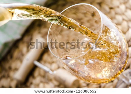 White wine being poured into a glass. - stock photo