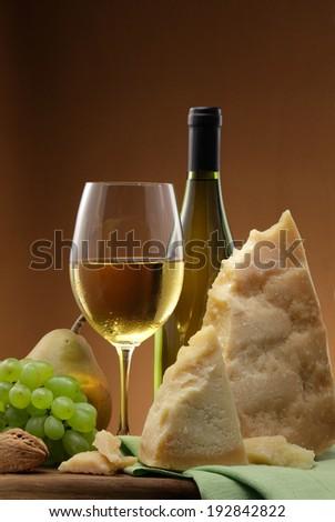 White wine bottle,  white wine glass, white wine grapes and parmegiano cheese still life - stock photo