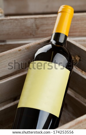 White wine bottle with empty label in wooden crate - stock photo