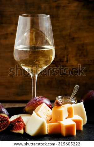 White wine, cheese, figs, nuts and grapes on the old wooden background, still life, selective focus - stock photo