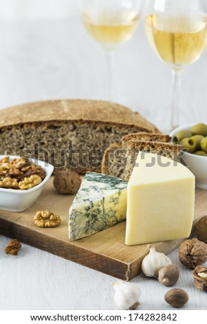 White Wine, cheese, nuts, olives, bread and garlic on wooden table - stock photo