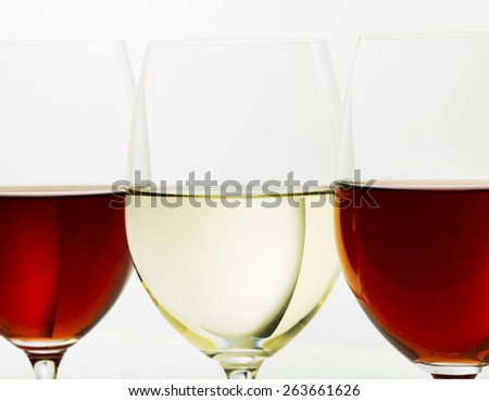 White wine glass among red ones - stock photo