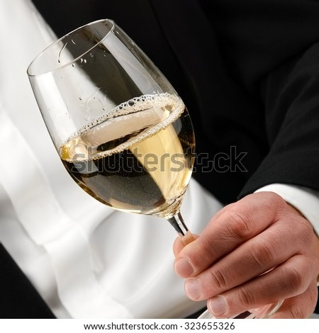 White wine glass in a man hand