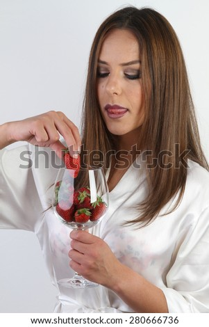 white wine glass of crystal full of fresh organic red nature strawberries - a beautiful young smiling brunette with large breasts in a white sexy silk peignoir - stock photo