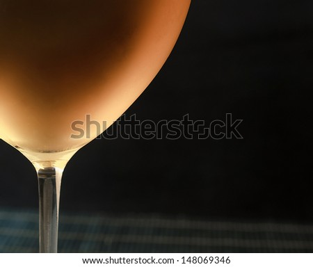White wine in glass, black background