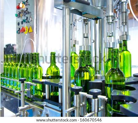 white wine in glass bottling machine at winery - stock photo