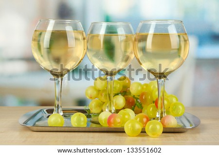 White wine in glass on salver on room background - stock photo
