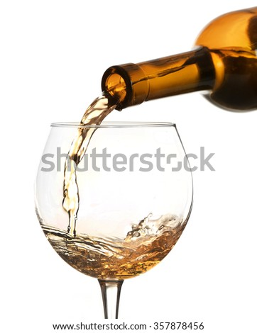 White wine pouring in glass, isolated on white - stock photo