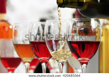 White wine pouring into glasses, closeup - stock photo