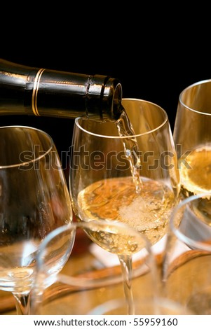 White wine pouring on glasses on a party. Black background