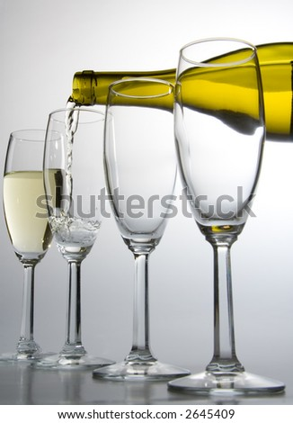 white wine pours from bottle into wineglass