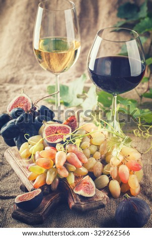 White wine,red wine in glasses and grapes with Ingram.Still life. Toned image. Vintage style.selective focus.