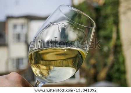 White wine swirling in a crystal glass outdoors - stock photo