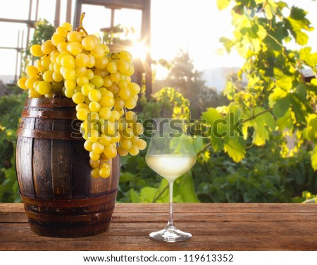 White wine with grapes and barrel on wood table