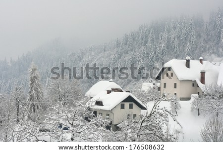 White winter in a small village in the alps during snowfall - stock photo