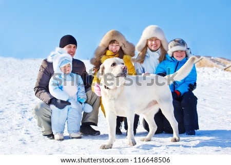 White winter labrador dog and family beside him - stock photo
