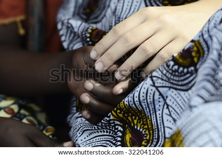 White woman holds hands with a little native African girl, in Bamako, Mali. A black child and a white woman hold hands. A beautiful shot with lots of possible background symbols. No to Racism!  - stock photo